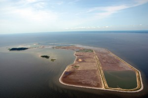 Aerial Image of Poplar Island Restoration in the Chesapeake Bay, accompanied by the Army Corps of Engineer's list of Beneficial Uses of Dredge for Engineering, Agriculture, Product and Environmental Enhancement Applications. Located in the Chesapeake Bay, Poplar Island is a flagship example of the USACE's beneficial uses of dredge. Working with state and federal organizations, the USACE has been placing dredged sediments from The Port of Baltimore's shipping channels onto the island since the mid-90's. This practice meets the Port's immediate need for a dredge disposal site while symbiotically creates much needed habitats for fish and wildlife, at a time when such habitat is threatened due to sea level rise. Over approximately 18 years, 40 million cubic yards of dredge material will be placed here to create 1,140 acres of manufactured island.